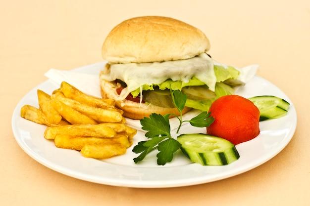 Cheeseburger com batatas fritas, pepinos fatiados e tomates