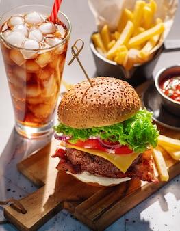 Cheeseburger com carne, queijo, tomate, cebola e alface e um copo de refrigerante gelado e batatas fritas.