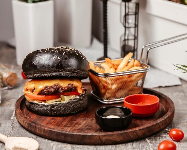 Cheeseburger com pão preto e batatas fritas