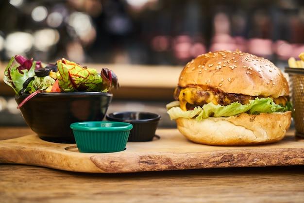 Cheeseburger com salada na mesa de madeira