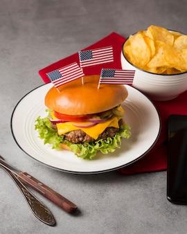 Cheeseburger de ângulo alto no prato com bandeira americana e batatas fritas