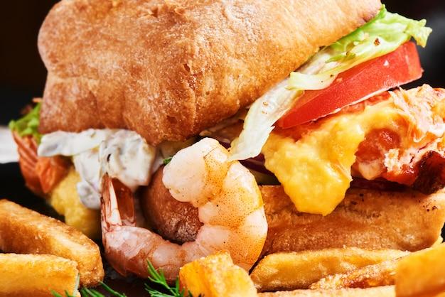 Cheeseburger de jantar recheado com camarão, queijo e legumes e batata frita
