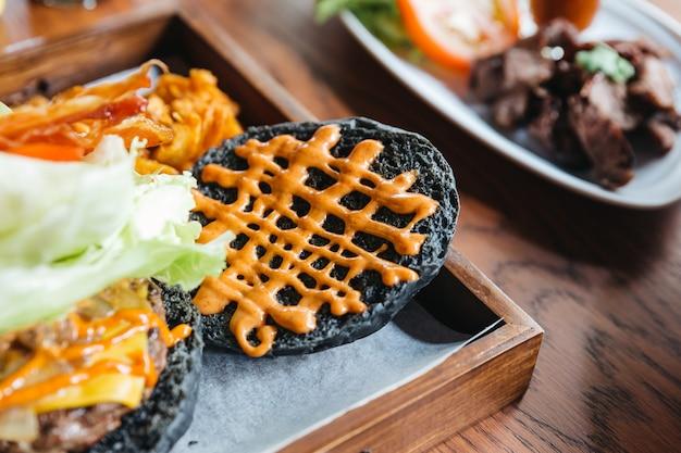 Cheeseburger do carvão vegetal do close-up com bacon crocante, couve, cebola, tomate, servido com faca e forquilha na tabela de madeira.