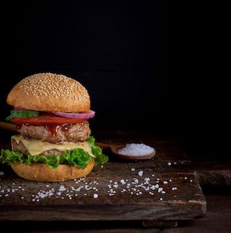 Cheeseburger em um pão com sementes de gergelim, no meio legumes frescos