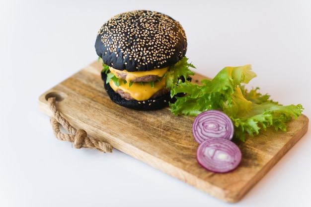 Cheeseburger preto na placa de desbastamento de madeira, fundo cinzento.