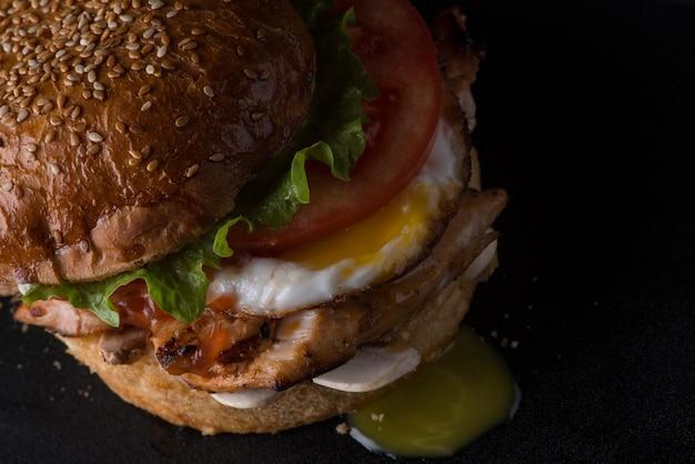 Cheeseburger suculento amarrotado em uma superfície preta, vista de cima, close-up