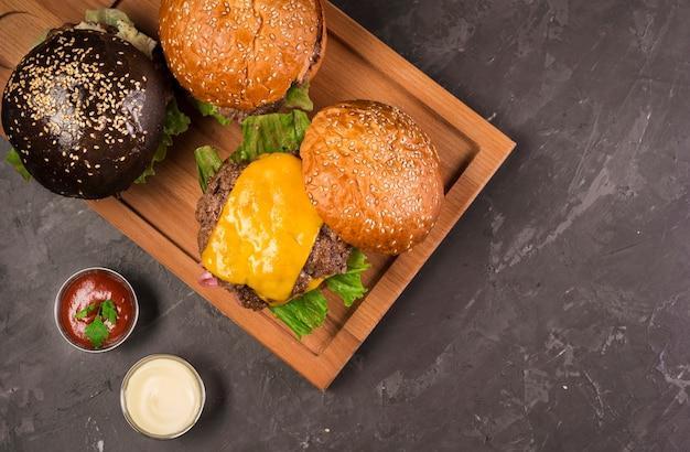 Cheeseburgers de vista superior em uma placa de madeira