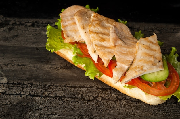 Cheeseburguer em uma velha superfície de madeira de cor escura hambúrguer com carne de frango em uma velha madeira