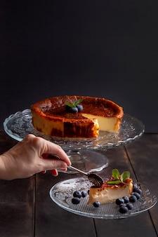 Cheesecake caseiro basco queimado com cream cheese, ovos e creme de leite assado em uma crosta miúda, com mirtilos e folhas de hortelã. mulher quebra um pedaço em um prato na superfície escura.