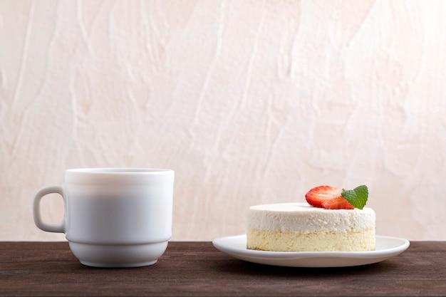 Cheesecake clássico de nova york com morangos e uma xícara de café ou chá.