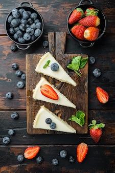 Cheesecake clássico de nova york, fatiado, na velha mesa de madeira escura