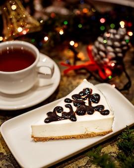 Cheesecake com cobertura de chocolate e xícara de chá