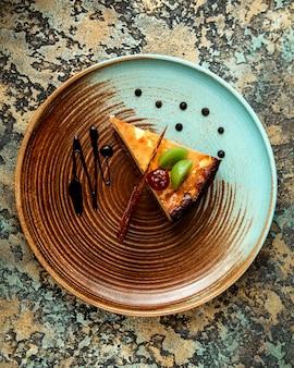 Cheesecake com fatia de cereja vidrada com kiwi e açúcar caramelizado