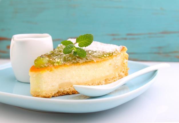 Cheesecake com kiwi em um prato decorado com hortelã