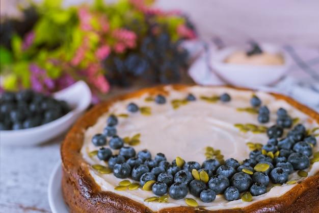 Cheesecake com mirtilo, sementes de abóbora e creme