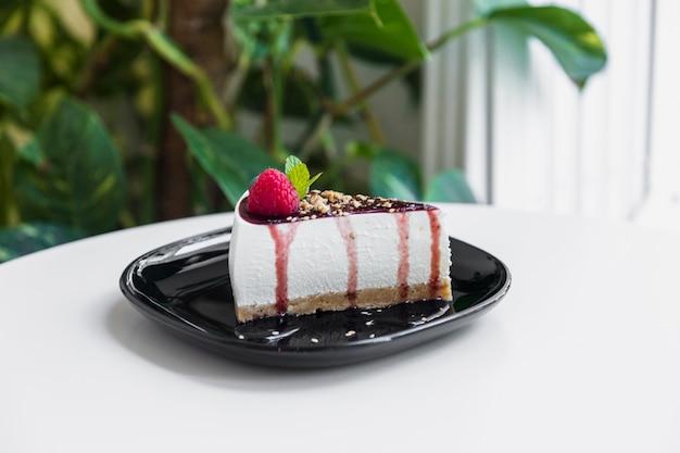 Cheesecake com molho de frutas e hortelã verde na placa preta sobre a mesa branca