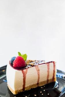 Cheesecake com molho de frutas e hortelã verde sobre fundo preto contra um fundo branco