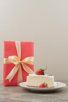 Cheesecake com morangos e um presente na mesa de mármore.