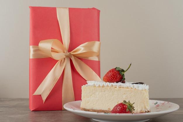 Cheesecake com morangos e um presente na mesa de mármore