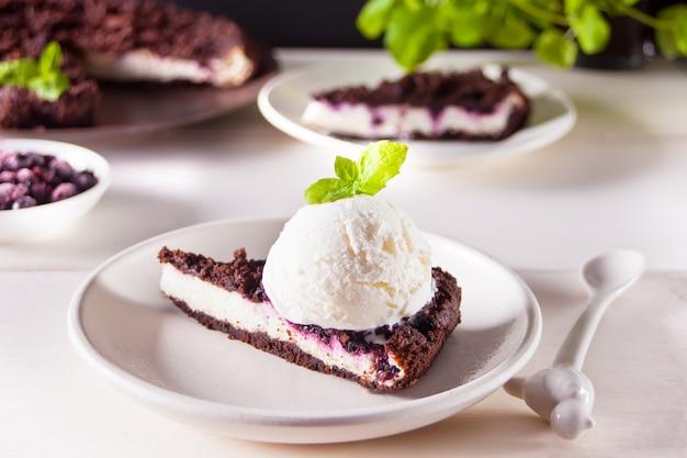 Cheesecake cremoso com chocolate, groselha preta, sorvete e folhas de hortelã para decoração