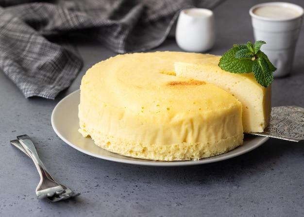 Cheesecake de algodão japonês com hortelã em um prato cinza.