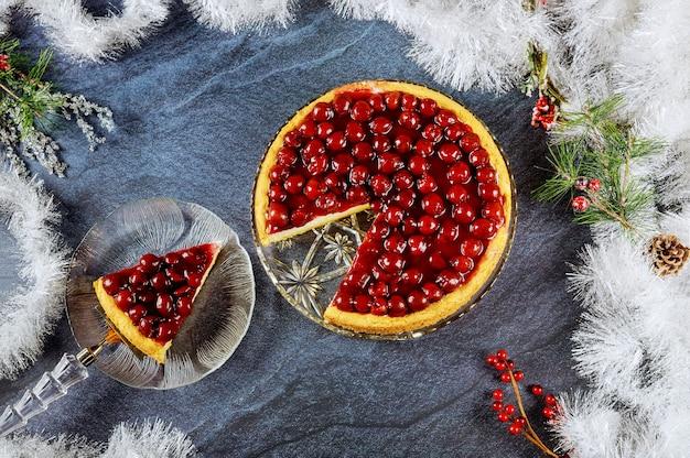 Cheesecake de cereja com frutas vermelhas no topo com decoração de cristmas.