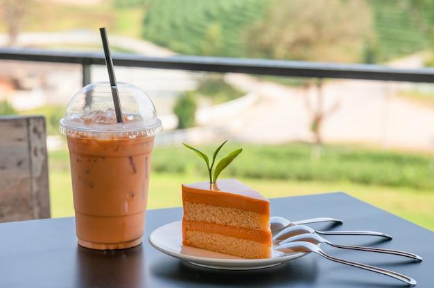 Cheesecake de chá tailandês laranja com bebida de chá tailandês de gelo na mesa de madeira na plantação