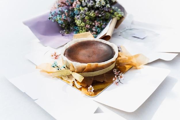 Cheesecake de chocolate basco queimado com buquê de flores na mesa.