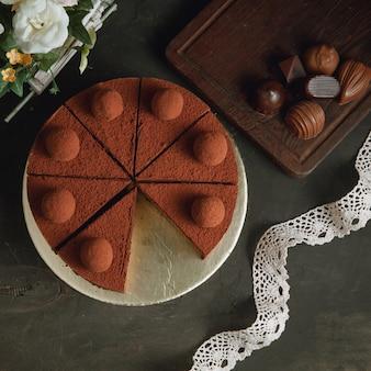 Cheesecake de chocolate com trufas e bombons de chocolate em fundo preto