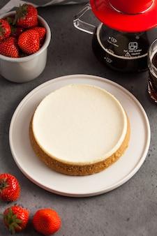 Cheesecake de coco em um prato redondo. tbule com café preto e uma caneca de morangos frescos.