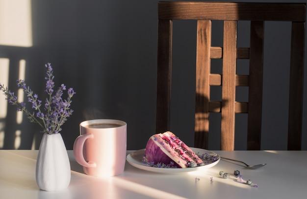 Cheesecake de mirtilo e lavanda no prato e xícara de chá na mesa branca