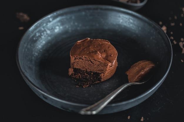 Cheesecake de muffin de chocolate no prato escuro com garfo