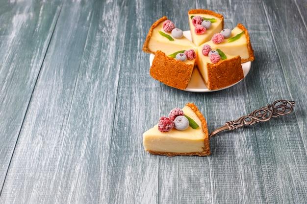 Cheesecake de newyork caseiro com frutas congeladas e hortelã, sobremesa orgânica saudável, vista superior