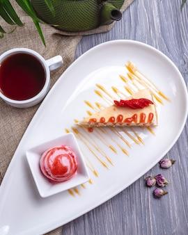 Cheesecake de sobremesa com vista superior e sorvete de morango e fatias ‹morangos com uma xícara de chá na mesa