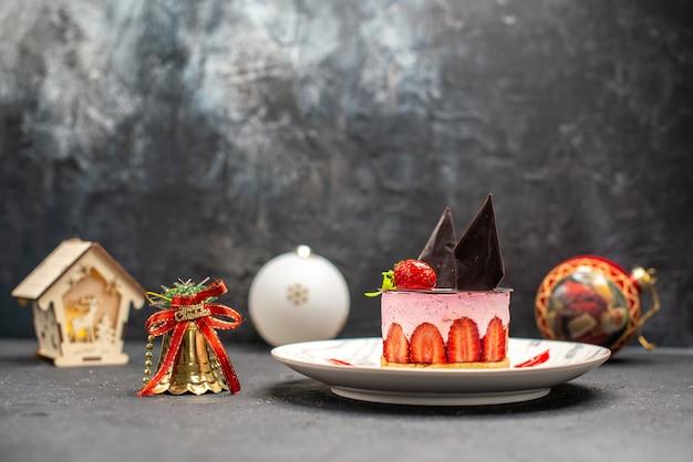 Cheesecake delicioso com morango e chocolate em uma placa oval. lanterna de brinquedos de natal no escuro.