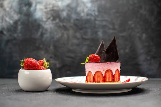 Cheesecake delicioso de frente com morango e chocolate em prato oval tigela de morangos no escuro