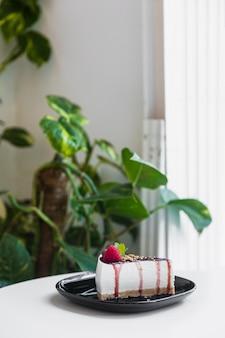 Cheesecake doce com bagas frescas na placa de cerâmica preta sobre a mesa branca