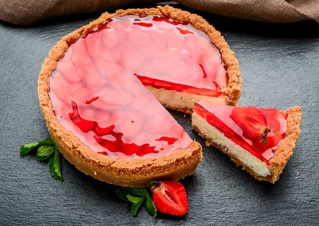 Cheesecake frio com morango e geléia de morango.