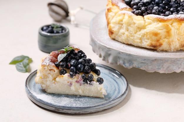 Cheesecake macio de mirtilo assado caseiro san sebastian, inteiro e fatiado