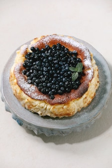 Cheesecake macio de mirtilo caseiro san sebastian em prato de cerâmica decorado
