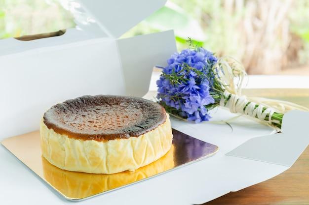 Cheesecake queimado basco com buquê de hortênsia na mesa de madeira.
