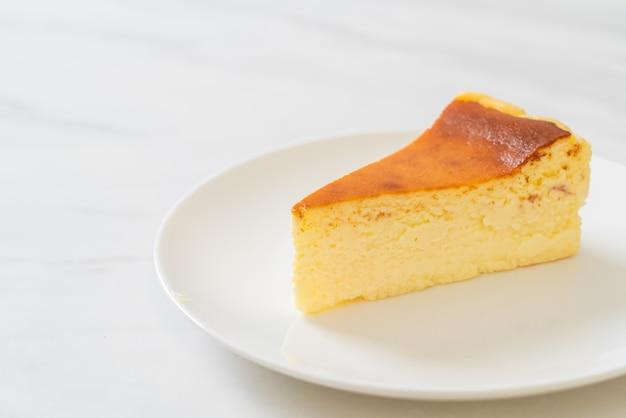 Cheesecake queimado caseiro em prato branco Foto Premium
