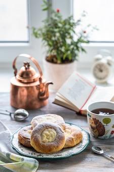 Cheesecake rola no café da manhã em uma mesa de madeira perto da janela com um gato