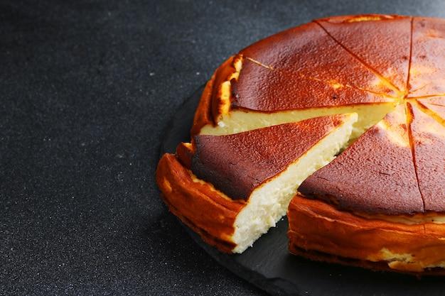 Cheesecake san sebastian close-up na mesa escura.
