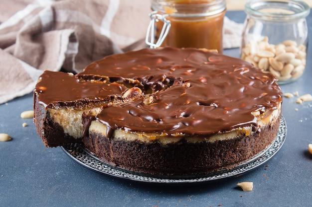 Cheesecake snickers com caramelo, nougat e amendoim layered bolo na backgro azul de concreto