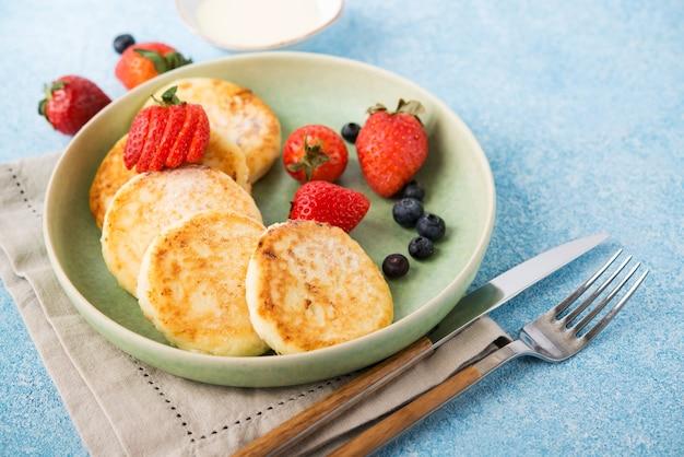 Cheesecakes caseiros fritos com leite condensado e frutas vermelhas, copie o espaço