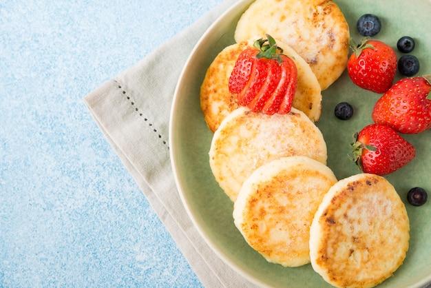 Cheesecakes caseiros fritos com leite condensado e frutas vermelhas, vista de cima, copie o espaço