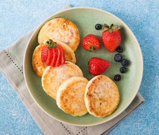 Cheesecakes caseiros fritos com leite condensado e frutas vermelhas, vista de cima