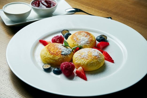 Cheesecakes caseiros ou syrniki com geléia, frutas frescas e creme de leite em um prato branco. cozinha ucraniana. comida de café da manhã