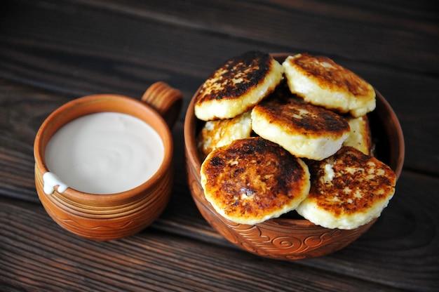 Cheesecakes com creme de leite em cerâmica sobre uma mesa de madeira
